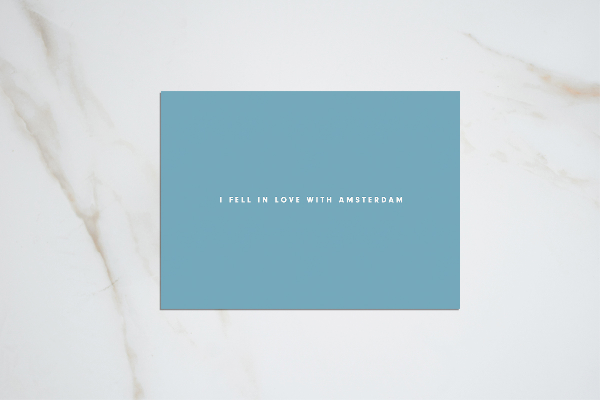 I fell in love with Amsterdam - light blue postcard